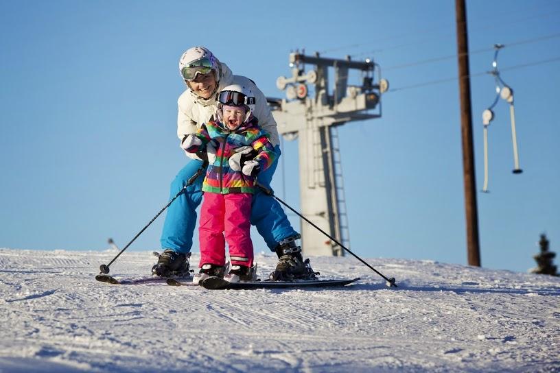 Barn og voksen kjører ski